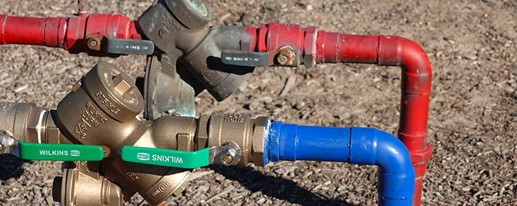 Red and blue water lines with backflow preventer